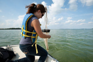 Student pulls up a plankton net from Lake Mendota