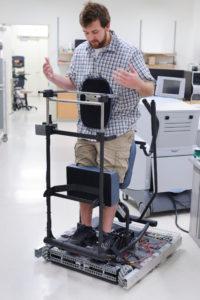 Student demonstrates a standing-paraplegic omni-directional transport device.